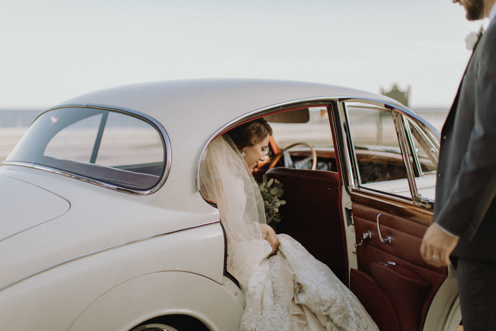 Bride getting into vintage car in Bay St. Louis, Mississippi
