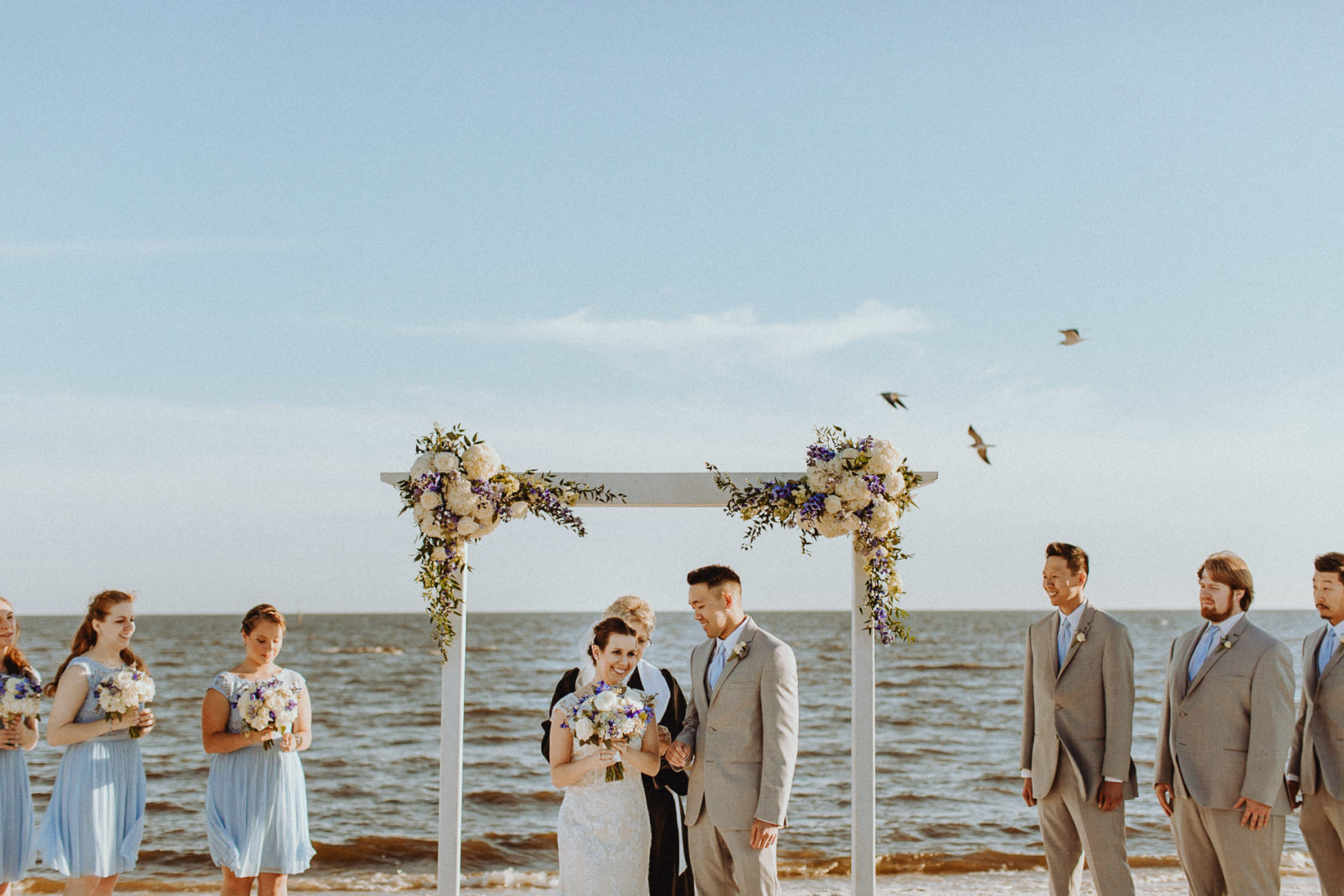 Biloxi Beach wedding ceremony with birds flying in the background