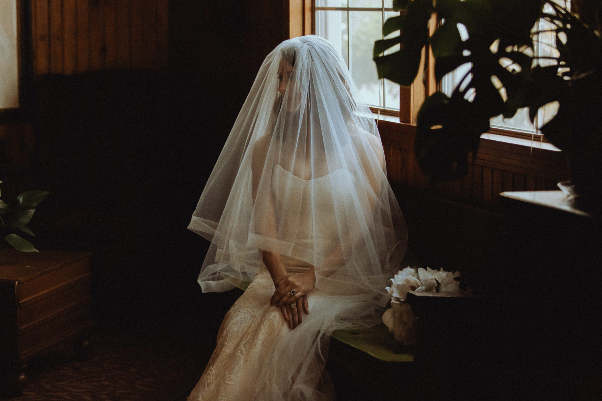 Bride covered in veil sitting alone in the dark